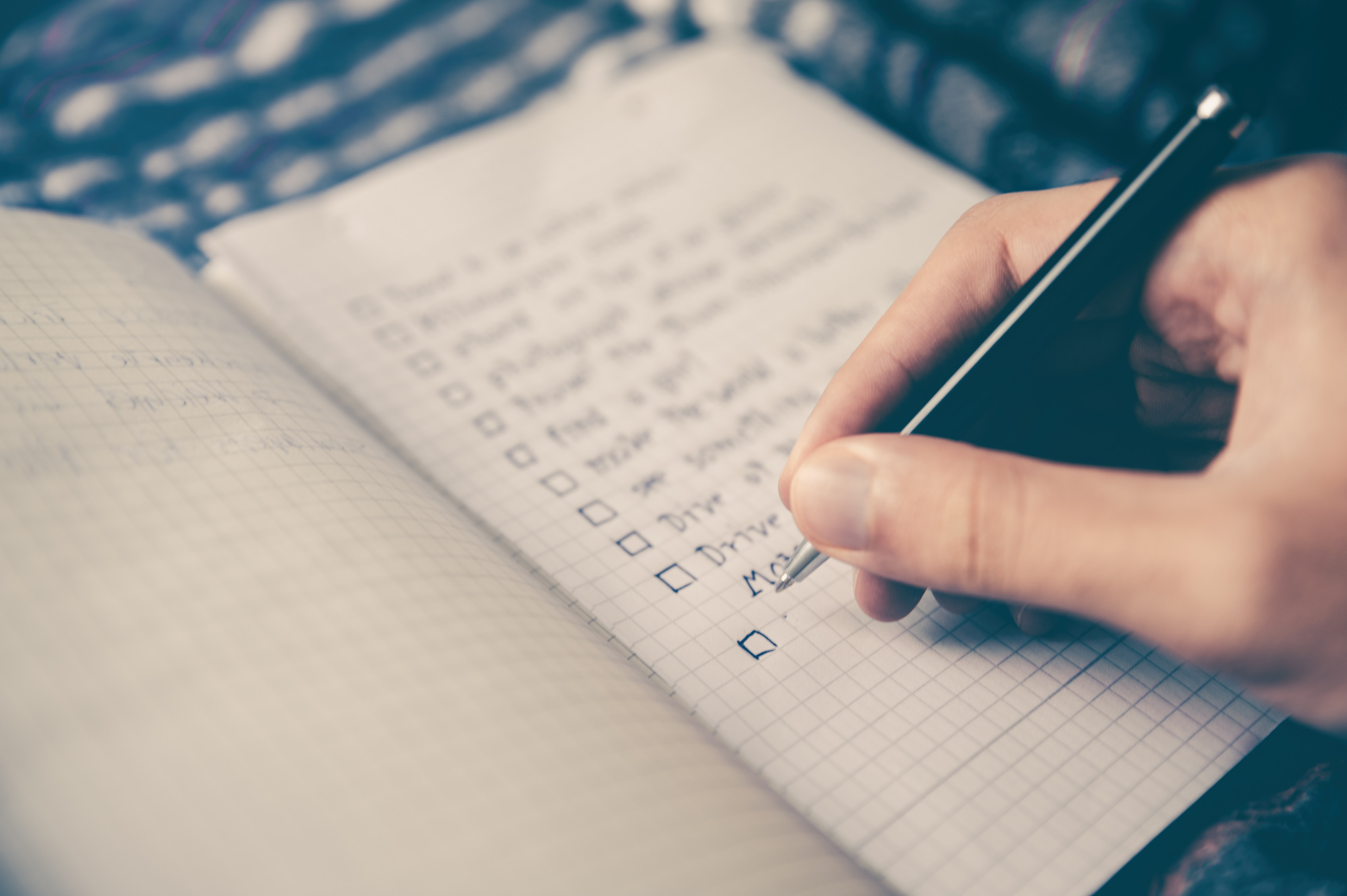 A hand writing in a square-ruled notebook with a black pen.