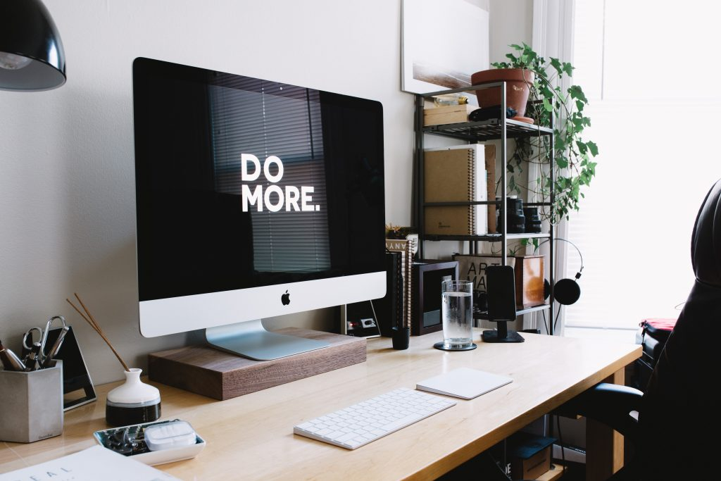 "Text ""DO MORE"" on an iMac screen on top of a minimalist office desk."