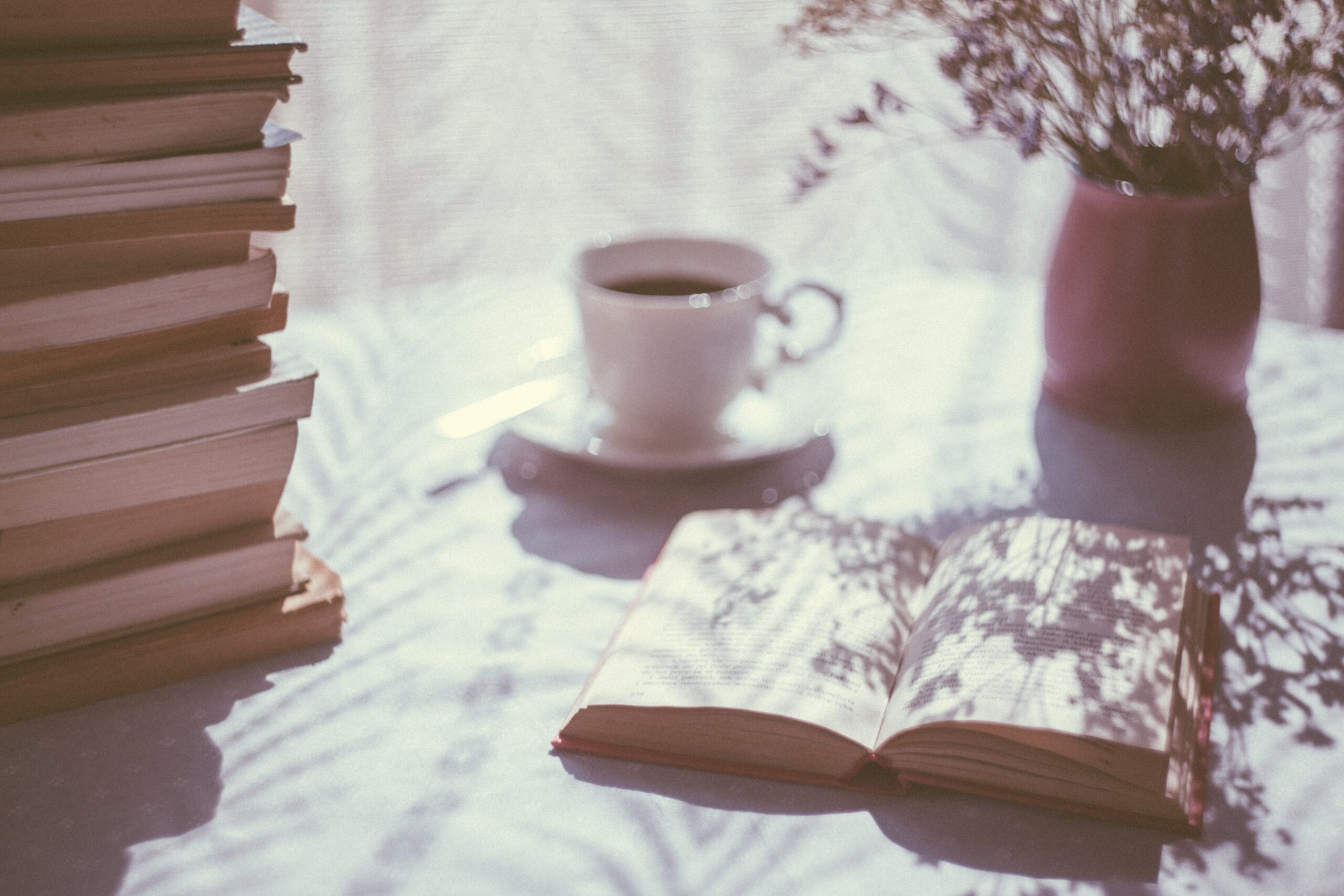 A table of books with a cappuccino cup and a vase of dried flowers on a white table cloth infant of white curtain. There is a shadow casting over the table and one of the books, the only open book on the table.